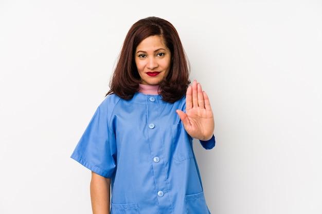 Женщина медсестры среднего возраста латинская изолировала стоять с протянутой рукой показывая знак стопа Premium Фотографии