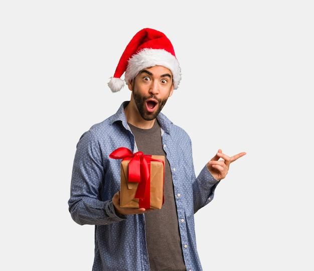 手で何かを保持しているサンタの帽子を着ている若い男 Premium写真