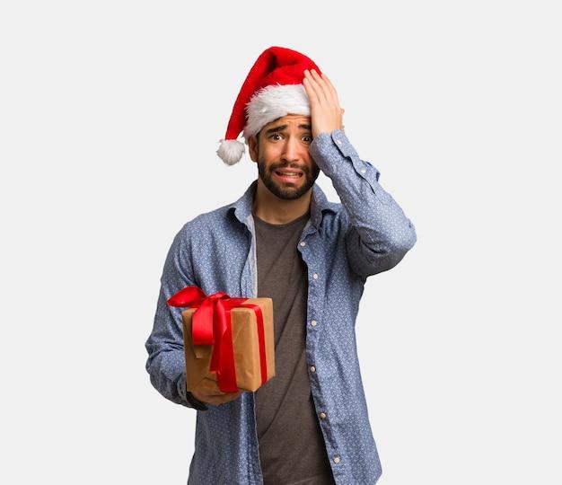 若い男は、忘れて、何かを実現するサンタの帽子を着て Premium写真