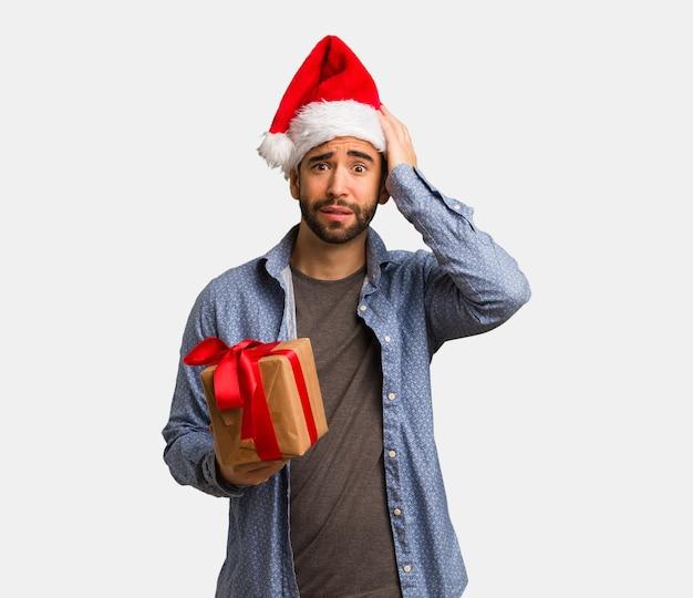 サンタの帽子を身に着けている若い男は心配して圧倒した Premium写真