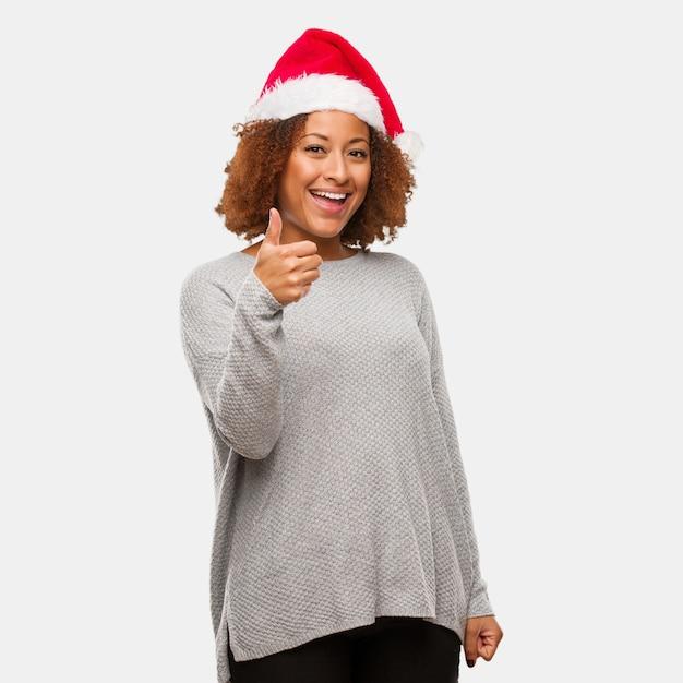 笑顔と親指を上げるサンタの帽子を身に着けている若い黒人の女性 Premium写真
