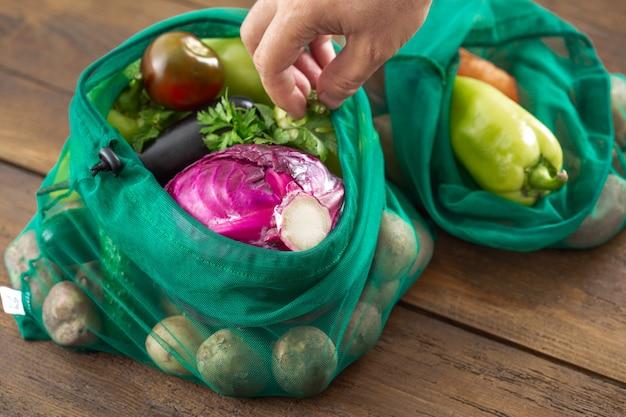 ビニール袋のコンセプトはありません。木製のテーブルに野菜の盛り合わせの食料品のメッシュバッグ Premium写真