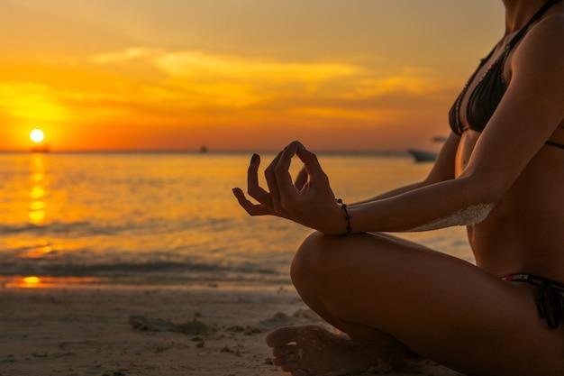 Женщина делает медитации на пляже на закате Premium Фотографии