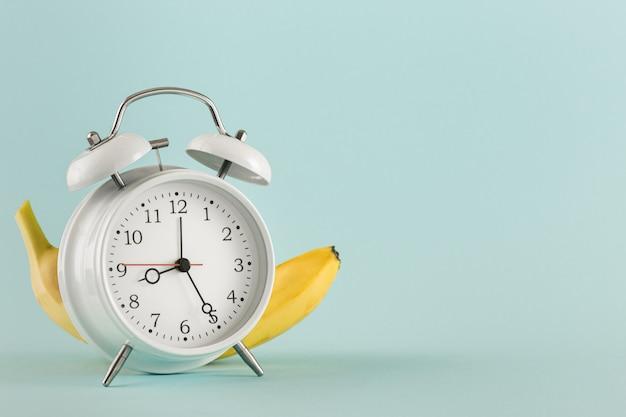 教育コンセプトあなたのテストのための古い目覚まし時計バナナの場所 Premium写真