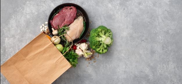 Продовольственная сумка для покупок с видом сверху здоровой пищи на конкретном пространстве копии Premium Фотографии
