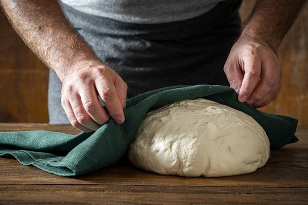 自家製のパンを焼く新鮮な生地を調理した男 Premium写真