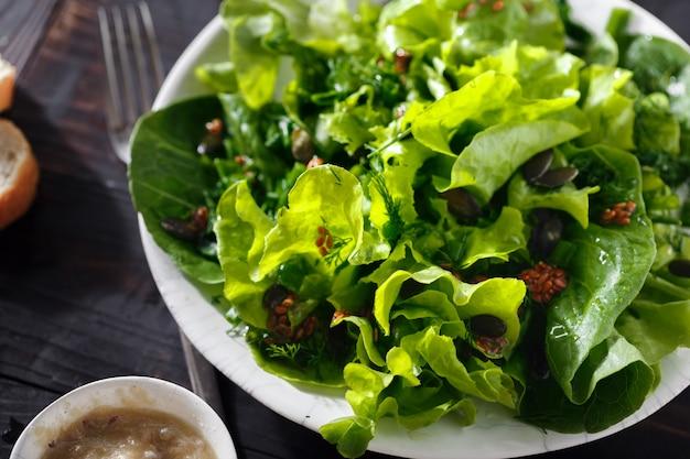 Тарелка свежего зеленого салата из семян льна темного дерева диетическое питание Premium Фотографии