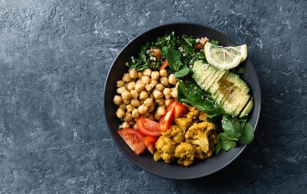 Вегетарианская здоровая еда с нутом, помидорами, авокадо и шпинатом Premium Фотографии