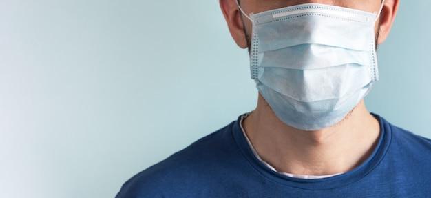 Человек в медицинской защитной маске на светлой стене. коронавирус и эпидемия Premium Фотографии