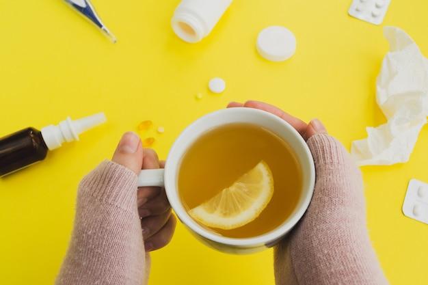 風邪とインフルエンザの季節。お茶と薬のマグカップを持つ女性 Premium写真