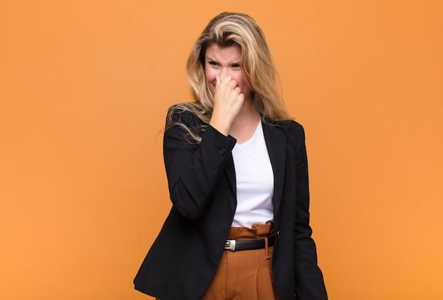 Чувствуя отвращение, держась за нос, чтобы не чувствовать неприятный запах и неприятный запах Premium Фотографии