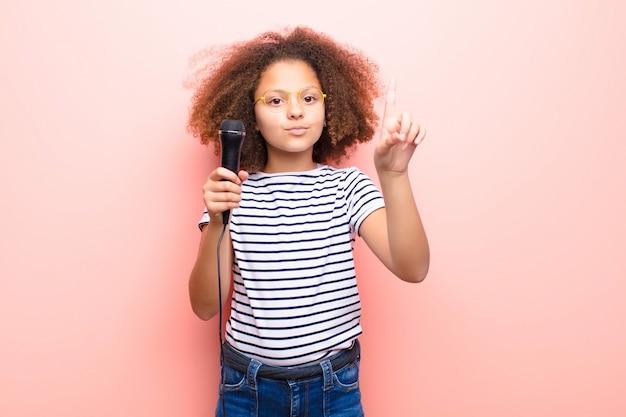 マイクを使って平らな壁にアフリカ系アメリカ人の女の子 Premium写真