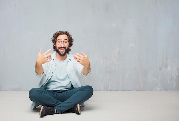 若い、ひげそり、床に座っている男。壁紙の背景 Premium写真