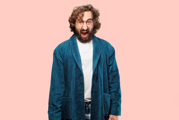 バスローブの夜のスーツを着ている若い男が怒っているポーズ Premium写真