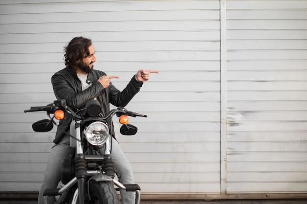 彼のビンテージバイクの若いオートバイライダー Premium写真
