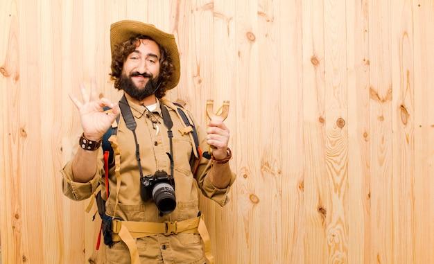 麦わら帽子と木製の背景にバックパックの若いクレイジーエクスプローラー Premium写真