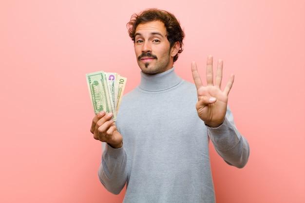 ピンクの平らな壁にドル紙幣で若いハンサムな男 Premium写真
