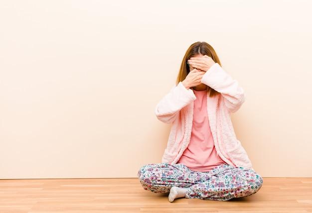 Молодая женщина в пижаме сидит дома закрывая лицо обеими руками Premium Фотографии