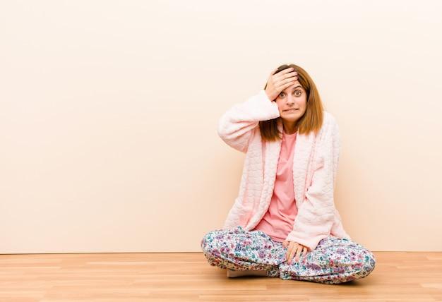 忘れられた締め切りにパニックに陥り、ストレスを感じ、混乱や間違いを隠さなければならないパジャマを着た若い女性 Premium写真