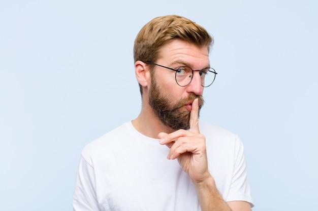 Молодой белокурый взрослый мужчина просит тишины и покоя, жестикулирует пальцем перед ртом, говорит тссс или держит в секрете Premium Фотографии