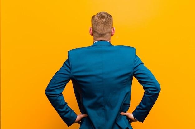 Молодой рыжий бизнесмен, чувство смущения или полный или сомнения и вопросы, интересно, с руки на бедрах, вид сзади Premium Фотографии