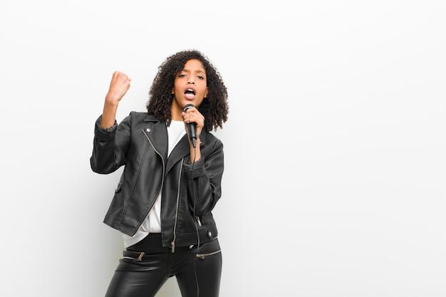 革のジャケットを着てマイクを使って若いかなり黒人女性 Premium写真