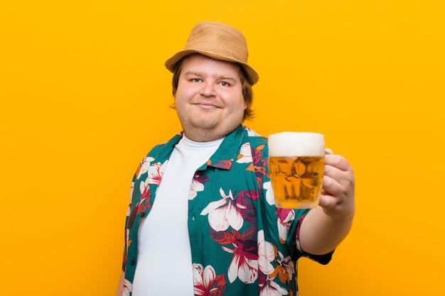 平らな壁にビールのパイントを持つ若い大きなサイズの男 Premium写真
