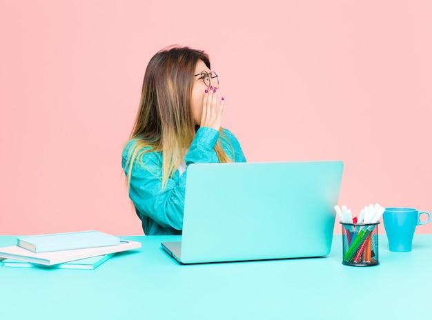 口の横に手で、側にスペースをコピーするために大声で怒って叫んでラップトップで働く若いきれいな女性 Premium写真