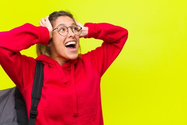 若い可愛い学生、口を開けて、ひどい間違いのために恐ろしくてショックを受けて、手を頭に上げて Premium写真