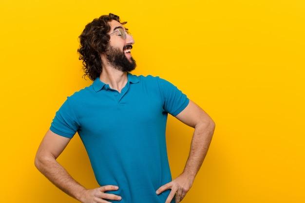 幸せ、陽気、自信を持って、誇らしげに笑顔と腰に両手で側に見て若い狂った男 Premium写真