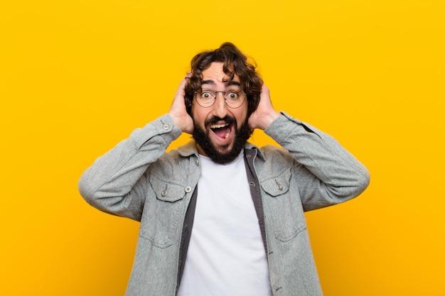 Молодой сумасшедший человек поднимает руки к голове, с открытым ртом, чувствуя себя чрезвычайно счастливым, удивленным, взволнованным и счастливым Premium Фотографии