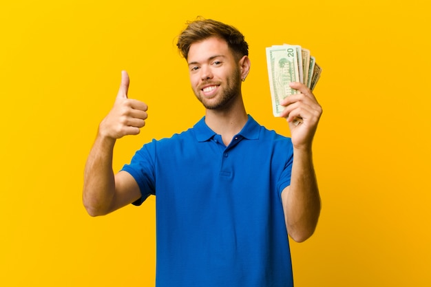 オレンジの紙幣と若い男 Premium写真