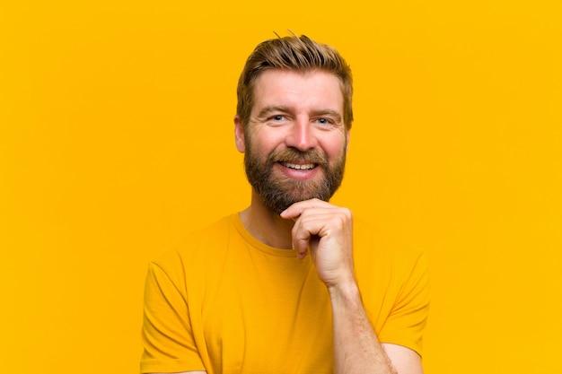 幸せと笑顔のあごに手を探して、疑問に思って、オプションのオレンジ色の壁を比較する若いブロンドの男 Premium写真