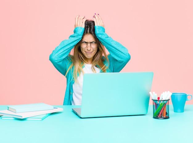 頭と両手を上げて、頭痛でストレスや不安、落ち込んでイライラした感じのラップトップで働く若いきれいな女性 Premium写真