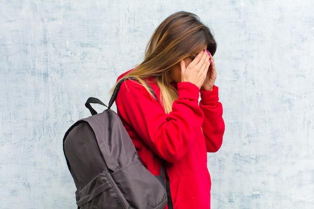 悲しい、欲求不満の絶望、泣いて、サイドビューの手で目を覆っている若いきれいな学生 Premium写真