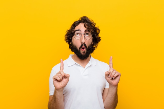 Молодой сумасшедший человек, выглядящий потрясенным, пораженным и открытым ртом, указывая вверх обеими руками, чтобы скопировать пространство желтой стены Premium Фотографии