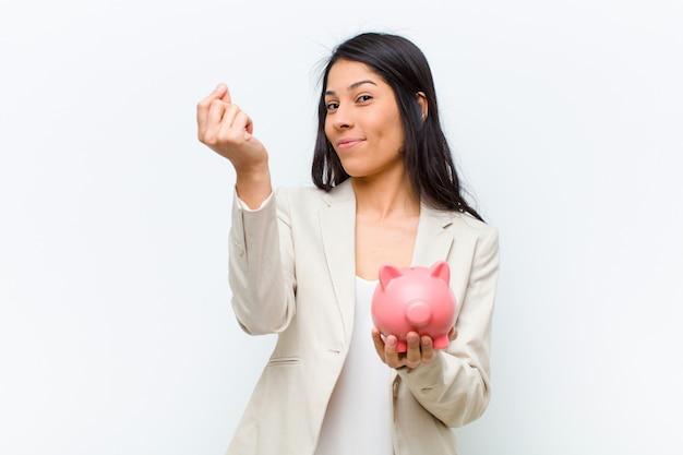 貯金箱と若いヒスパニック系きれいな女性 Premium写真