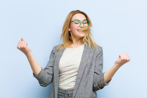 Молодая красивая белокурая женщина выглядит очень счастливой и удивленной, празднуя успех, крича и прыгая плоская стена Premium Фотографии