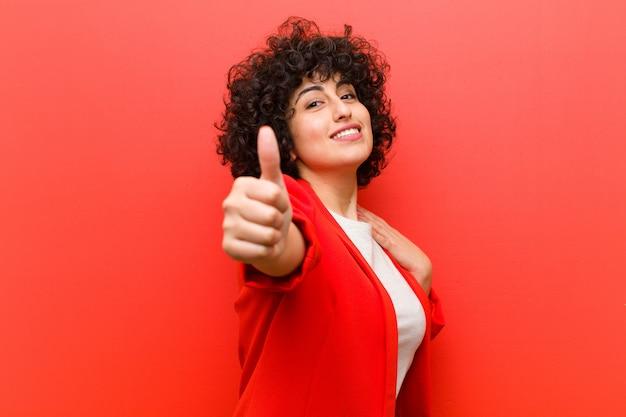 Молодая красивая афро женщина чувствует себя гордой, беззаботной, уверенной и счастливой, позитивно улыбаясь с большими пальцами вверх Premium Фотографии