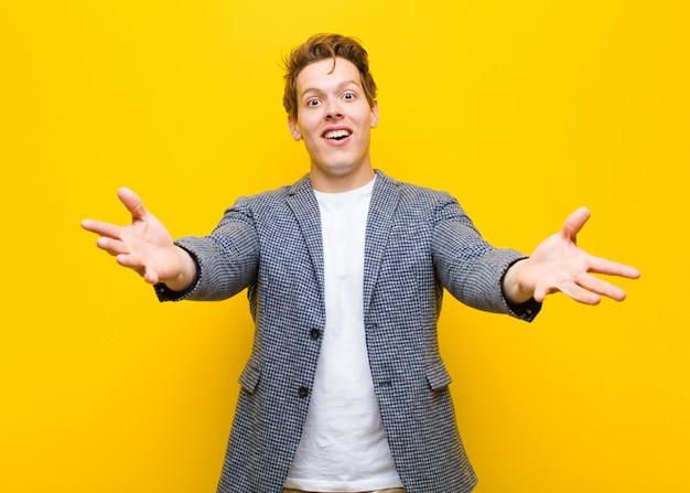 Молодой рыжеволосый мужчина весело улыбается, давая теплые, дружеские, любящие приветственные объятия, чувствуя себя счастливым и восхитительным оранжевым Premium Фотографии