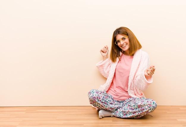 自宅で座っているパジャマを着た若い女性笑みを浮かべて、屈託のない、リラックスして幸せ、ダンスと音楽を聴いて、パーティーで楽しんで Premium写真