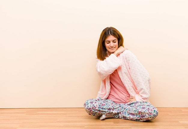 家で座っているパジャマを着た若い女性 Premium写真