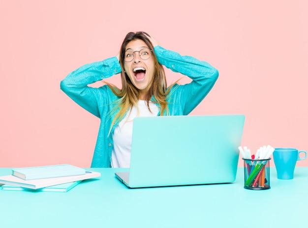Молодая красивая женщина работает с ноутбуком, поднимая руки к голове, с открытым ртом, чувствуя себя чрезвычайно счастливым, удивленным, взволнованным и счастливым Premium Фотографии