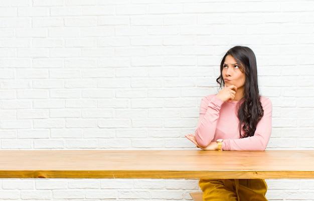 テーブルの前に座ってどの決定を下すのか疑問に思って、考えて、疑って混乱している、さまざまなオプションを持つ若いラテン女性 Premium写真