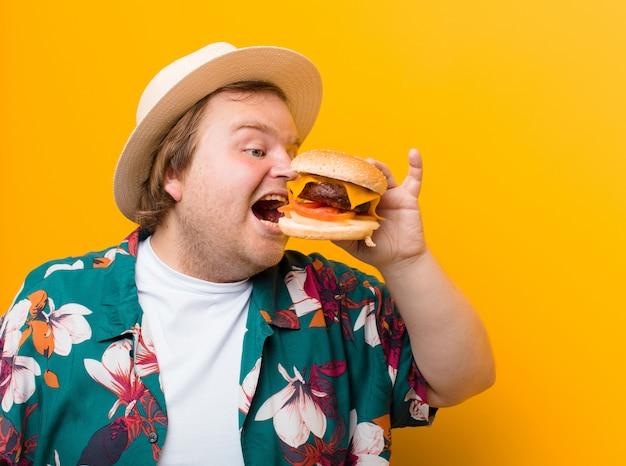 平らな壁にチーズハンバーガーを持つ若い大きなサイズの男 Premium写真