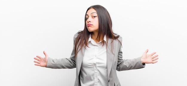 Молодая симпатичная женщина, чувствуя себя невежественной и смущенной, не имея ни малейшего представления, абсолютно озадачена тупым или глупым взглядом, изолированным на белой стене Premium Фотографии