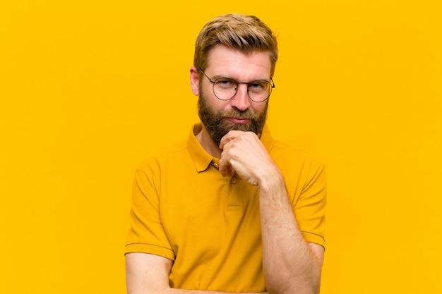 オレンジ色の壁に対して深刻な、混乱、不確実で思慮深く見て、オプションや選択肢の間で疑って若いブロンドの男 Premium写真