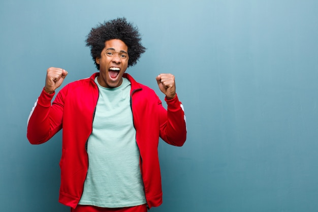 幸せ、驚き、誇りに思って、叫び、大きな笑顔で成功を祝っている若い黒人スポーツ男 Premium写真