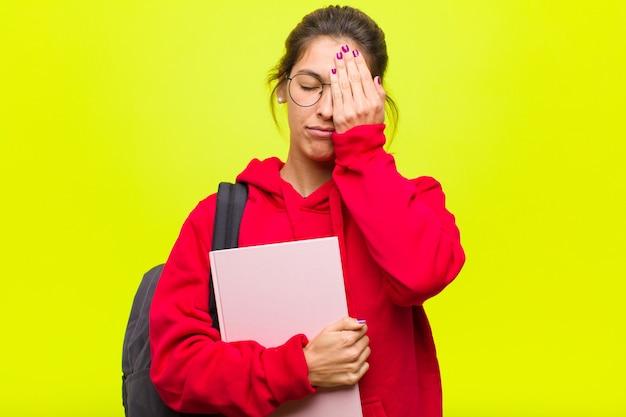 眠くて退屈してあくびをしている若い可愛い学生、頭痛と片手で顔の半分を覆っている Premium写真
