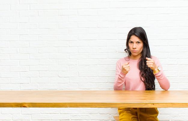 自信を持って、怒って、強く、攻撃的な探している若いかなりラテン女性、拳はテーブルの前に座ってボクシングの位置で戦う準備ができて Premium写真